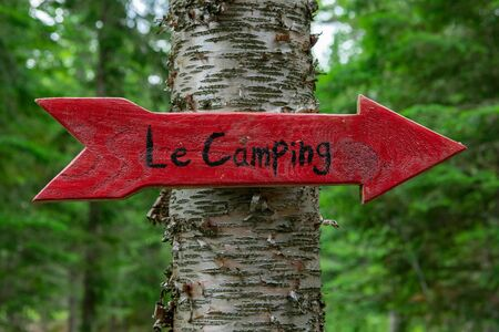 Diverse people enjoy spiritual gathering Directions to a rural forest campsite, a handmade French sign in the shape of a red arrow points mindful people towards a mystical retreat. Stock fotó