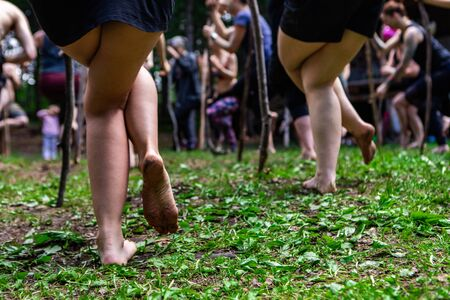 Diverse people enjoy spiritual gathering A closeup view on the bare legs of two woman, standing in the same posture during a yogic workshop in woodland at a retreat celebrating native cultures. Archivio Fotografico