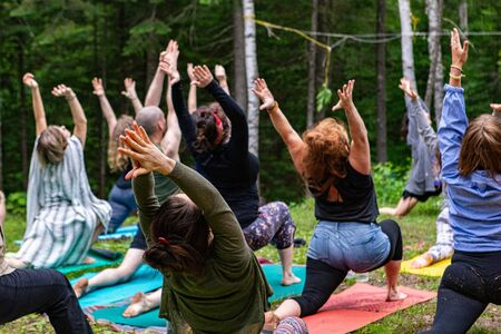 Diverse people enjoy spiritual gathering A group of people of all age groups are seen in warrior I pose (virabhadrasana I), during an outdoor yoga session as part of a multicultural celebration.