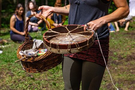 Diverse people enjoy spiritual gathering A close-up view of a young shaman woman holding a native drum and sacred objects in a wicker basket as she walk around a sacred site in a forest clearing. Archivio Fotografico - 131715991