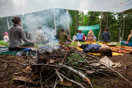 Diverse people enjoy spiritual gathering A close up view on a smoking campfire as blurred people are seen in the background, practicing mindful meditation and relaxation during a retreat to nature.