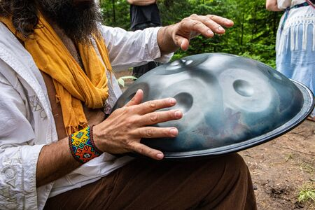 Diverse people enjoy spiritual gathering A close up view of an older shaman guy using his hands to play a sacred metal drum as people gather in nature to celebrate native cultures.