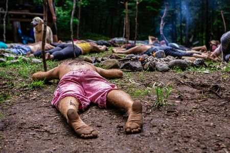Diverse people enjoy spiritual gathering People seeking enlightenment and spiritual guidance are seen lying flat on sacred ground in a woodland clearing at a shamanic and multicultural retreat.