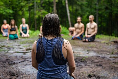Diverse people enjoy spiritual gathering A closeup and rear view of a woman with dark hair, kneeling on sacred ground in a forest clearing with a mixed group of people in deep meditation.