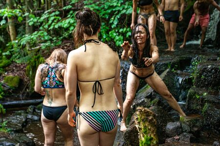 Diverse people enjoy spiritual gathering A playful and happy group of people are seen having a mud fight as they bathe in a woodland stream during a retreat dedicated to nature and spirituality.