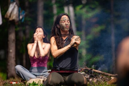 Diverse people enjoy spiritual gathering A young beautiful caucasian woman is seen covering her skin in sacred mud and clay during a shamanic ritual at a woodland retreat, with copy space.