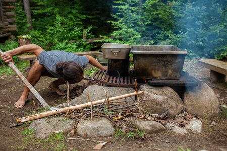 Diverse people enjoy spiritual gathering A barefooted man is seen close up, crouching as he starts a camp fire to cook healthy and natural food in a forest clearing during a weekend retreat to nature. Stock Photo