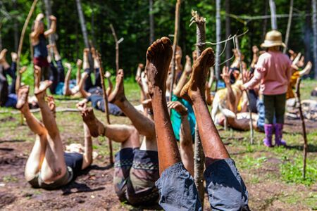 Diverse people enjoy spiritual gathering A multiethnic and intergenerational group of people are seen lying on backs with legs raised in air during a spiritual set of yoga poses in natural surroundings Archivio Fotografico