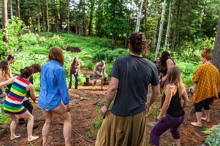 Diverse people enjoy spiritual gathering An intergenerational and colorful group of people are seen standing in a circle, experiencing playfulness and mindful dance during a spiritual getaway in nature