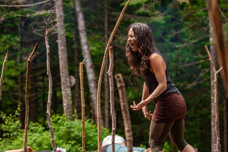 Diverse people enjoy spiritual gathering An inspirational caucasian woman is seen helping people through mindful yoga exercises during a woodland retreat, singing and shouting with room for copy. Archivio Fotografico - 131716135