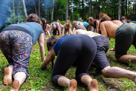 Diverse people enjoy spiritual gathering A multigenerational mix of individuals are seen in a circle, on all fours during a spiritual set of exercises for body and mind in natural surroundings.
