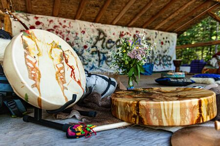 Diverse people enjoy spiritual gathering Traditional rawhide native drums and sacred objects are viewed close up at a sacred site in nature, with beater, colorful cushions and flowers.