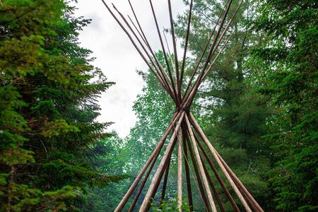 Diverse people enjoy spiritual gathering A closeup view on the parts of a teepee (tipi) tent, a traditional structure used by native tribes, conical in shape with smoke flaps sticking above tied string