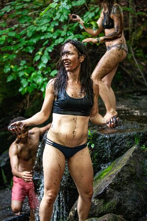 Diverse people enjoy spiritual gathering A mixed group of free spirited people are seen bathing and washing in a sacred river during a mindful retreat, playfully throwing mud and having fun.