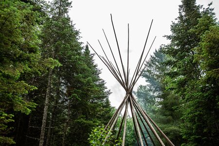Diverse people enjoy spiritual gathering The flops and pins of a tipi (teepee) tent are seen rising above green trees and vegetation in woodland as people gather to experience native tribal culture. Archivio Fotografico