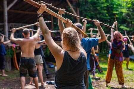 Diverse people enjoy spiritual gathering An eclectic mix of people are seen practicing mindful tai chi at a forest retreat dedicated to spirituality and native culture, with copy space. Archivio Fotografico - 131716100