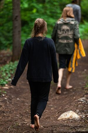 Diverse people enjoy spiritual gathering A young girl dressed in black with blonde hair is seen walking in bare feet along a forest path with blurry people in the background during a mindful retreat.