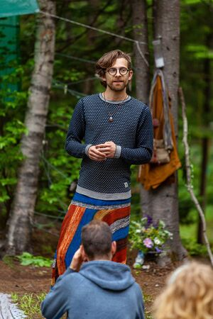 Diverse people enjoy spiritual gathering A confident shaman man wearing glasses and colorful clothes is seen standing over a group of people as he teaches native cultures and traditions in nature.