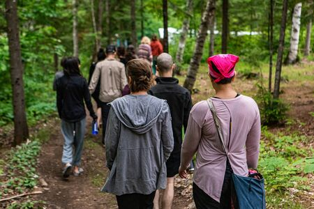 Diverse people enjoy spiritual gathering A large group of multigenerational people are seen from behind, walking together along a woodland trail during a multicultural and native retreat in nature.