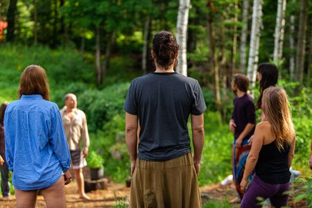 Diverse people enjoy spiritual gathering A multigenerational group of individuals are seen standing in a circle in a forest clearing as they practice shamanic and native traditions in nature.