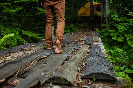 Diverse people enjoy spiritual gathering A barefooted person is seen close up, walking on a rustic wooden footbridge over a sacred woodland stream, wearing tanned colored jeans.