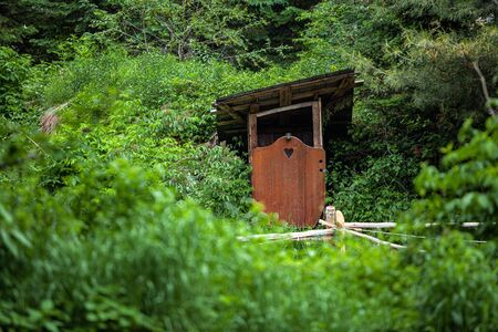 Diverse people enjoy spiritual gathering A quaint wooden restroom shack with wooden door and heart shape hole is seen in a woodland campsite, basic toilet facilities in rural area with copy space.
