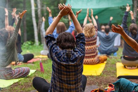 Diverse people enjoy spiritual gathering A multigenerational group of people wearing colorful clothes are seen from behind, sitting on yoga mats in a forest clearing as they experience meditation. Archivio Fotografico