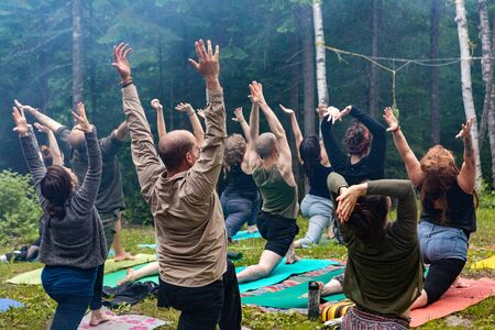 Diverse people enjoy spiritual gathering A multigenerational group of people are seen embracing traditional cultures in natural surroundings during a retreat for body and mind. Archivio Fotografico