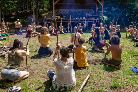 Diverse people enjoy spiritual gathering A multiethnic group of people from all age groups are seen together, practicing traditional tai chi & native exercises during a multicultural festival in nature