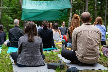 Diverse people enjoy spiritual gathering A multigenerational group of people are seen from behind, sitting on yoga mats during a shamanic ritual in woodland, seeking enlightenment and mindfulness.