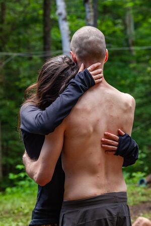 Diverse people enjoy spiritual gathering A man and woman are seen embracing each other at a woodland retreat dedicated to spirituality and mindfulness. Sweet couple hugging outdoors. 免版税图像