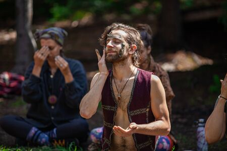 Diverse people enjoy spiritual gathering A spiritual leader is seen rubbing sacred clay into his face as blurry people follow his lead in the background, with room for copy. Stock Photo
