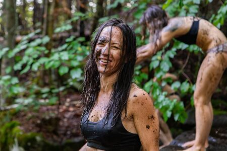 Diverse people enjoy spiritual gathering A close up portrait of a confident free spirited caucasian woman, covered in mud and sludge from a sacred stream in a forest during a spiritual retreat.