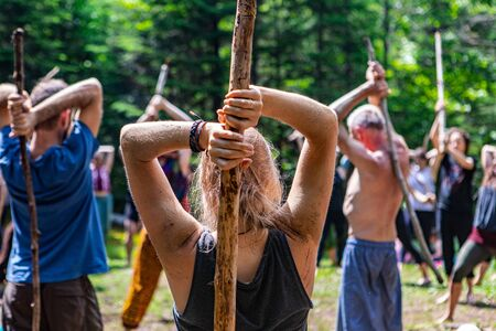 Diverse people enjoy spiritual gathering A close up and rear view of a fair skinned caucasian lady with mud stained clothes and shoulders, holding a stick as people practice sacred exercises in nature.