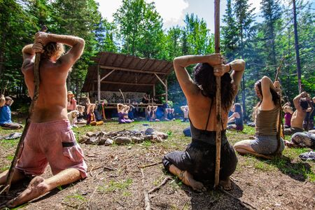Diverse people enjoy spiritual gathering An intergenerational group of mindful people are seen from behind, sat around a smoldering campfire as they practice traditional tai chi during a nature retreat