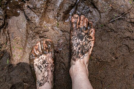 Diverse people enjoy spiritual gathering A top down view of a barefooted person standing in sacred mud and sludge during an outdoor retreat celebrating shamanic and native cultures. Stok Fotoğraf