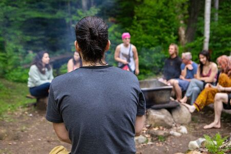 Diverse people enjoy spiritual gathering A closeup and back view of a caucasian guy with a hair bun and grey t-shirt, sitting around a campsite with a mixed group of people during a mindfulness retreat Stock Photo