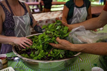 Diverse people enjoy spiritual gathering Hands of people are seen working together as they mix salad greens in a large bowl during a weekend retreat in nature celebrating health and wellness.