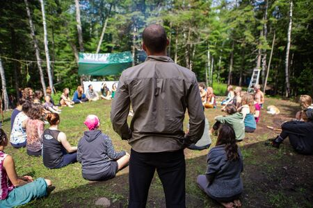 Diverse people enjoy spiritual gathering A spiritual leader is seen standing over a circle of open minded people seeking enlightenment and mindfulness during a multicultural festival in a forest. Archivio Fotografico