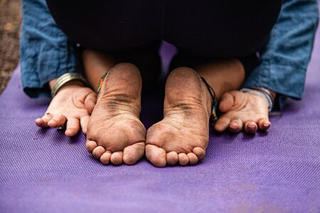 Diverse people enjoy spiritual gathering A closeup view on the mud stained bare feet of a woman experiencing spiritual awakening during a retreat in nature, meditating in yoga asana.