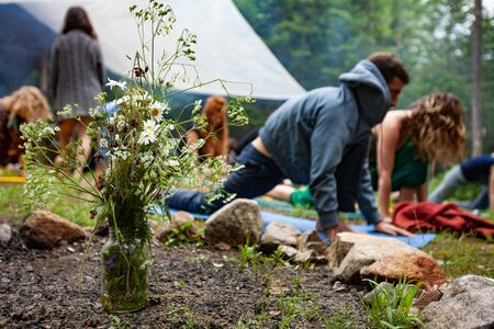 Diverse people enjoy spiritual gathering A blurry group of people are seen practicing mindful yoga postures together, behind a colorful arrangement of wildflowers at a weekend retreat in nature. Stock Photo