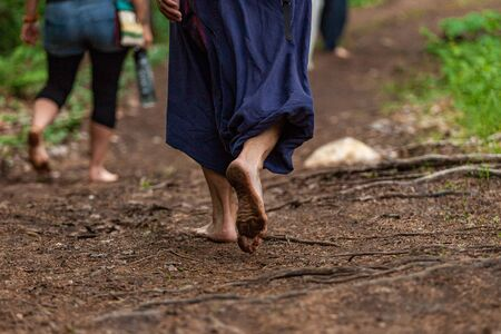 Diverse people enjoy spiritual gathering A close up view on the bare feet, covered in mud and dirt, as they walk on sacred soil during a spiritual exercise in woodland. Stok Fotoğraf