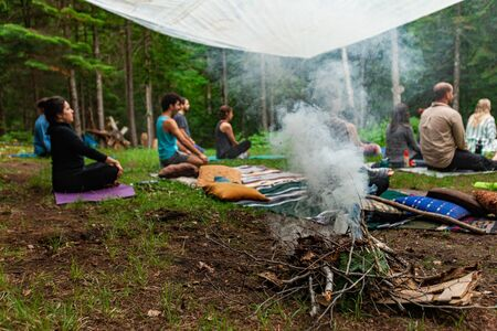 Diverse people enjoy spiritual gathering Blurred intergenerational people are seen experiencing deep meditation behind a small smoking camp fire of twigs and foliage, with copy space.