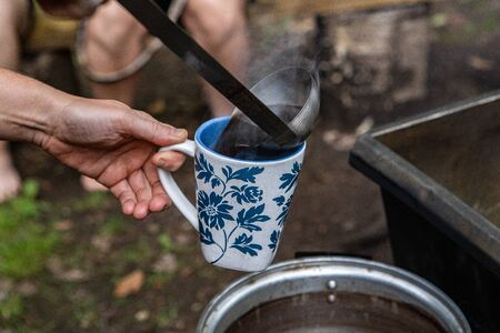 Diverse people enjoy spiritual gathering A close up view of a person using a ladle to serve steaming hot tea from a camp fire stove during a retreat dedicated to healthy body and mind.