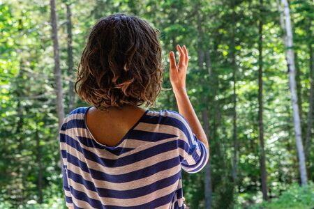 Diverse people enjoy spiritual gathering A young woman with shoulder length hair wearing a blue striped top is seen in meditation and relaxation, facing tall trees in dense woodland with copy space.