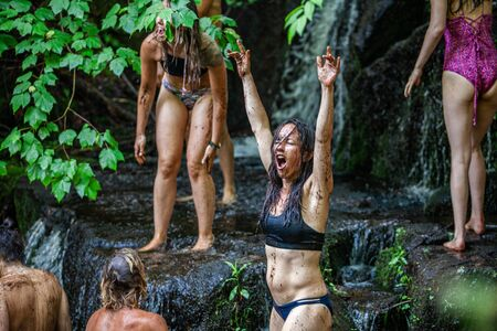 Diverse people enjoy spiritual gathering A free spirited and confident young caucasian woman is seen playful and ecstatic, covered in mud as she bathes in a natural river bed during a mindful retreat.