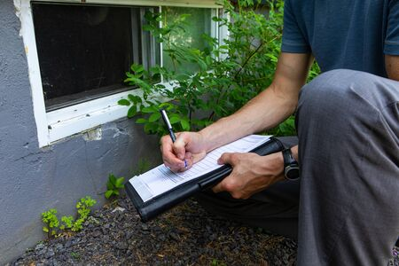 Indoor damp & air quality (IAQ) testing. A close up view of a building inspector checking exterior walls and windows of a domestic dwelling, using a pen and paper to fill regulation paperwork.