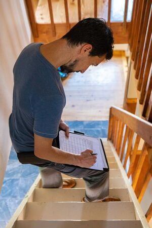 Indoor damp & air quality (IAQ) testing. A high angled view of a home inspector standing on stairs inside a family home, taking notes during an indoor environmental quality (IEQ) assessment.