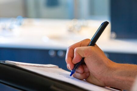 Indoor damp & air quality (IAQ) testing. A close up and side view on the hand of a caucasian man, using a pen and notepad during a building inspection, with room for copy and blurred background.
