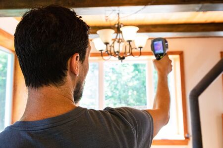 Indoor damp & air quality (IAQ) testing. A close up and rear view on a man carrying out an environmental quality assessment inside a domestic building, holding an infrared imaging camera.